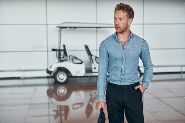 Against vehicle. Young man in formal wear is in modern airport. Conception of vacation - Stock Photo - Images