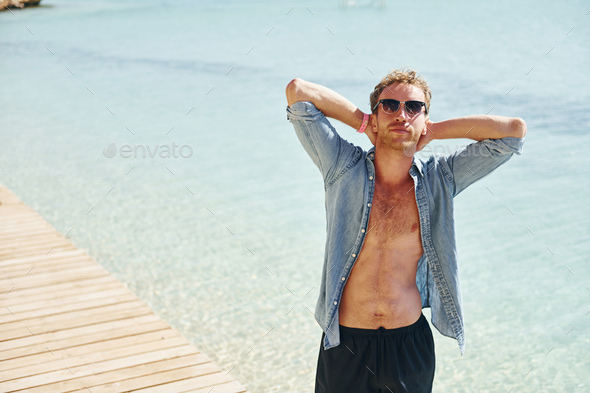 In sunglasses. Young european man have vacation and enjoying free time on the beach of sea - Stock Photo - Images