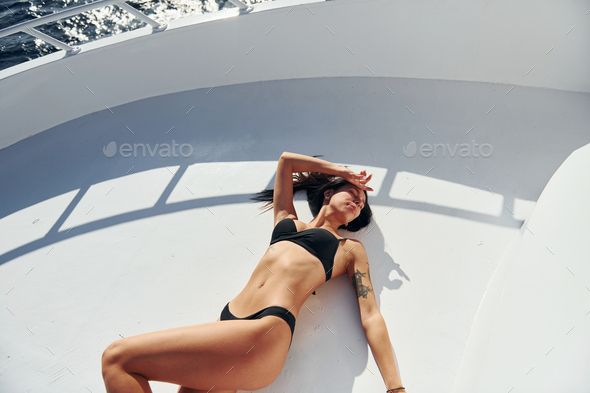 Young brunette in bikini is on the white yacht on the sea. Conception of vacation - Stock Photo - Images
