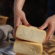 Somebody hands put pieces of  fresh homemade cheese on a wooden board - PhotoDune Item for Sale