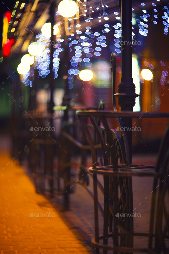 Fences and blurred night lights decorations of the bar on background. Christmas time in the city. - Stock Photo - Images