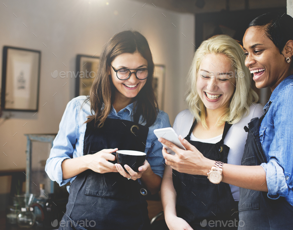 Baristas watching something funny on a phone - Stock Photo - Images
