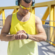 Young athlete checking time while standing on yellow bridge - PhotoDune Item for Sale