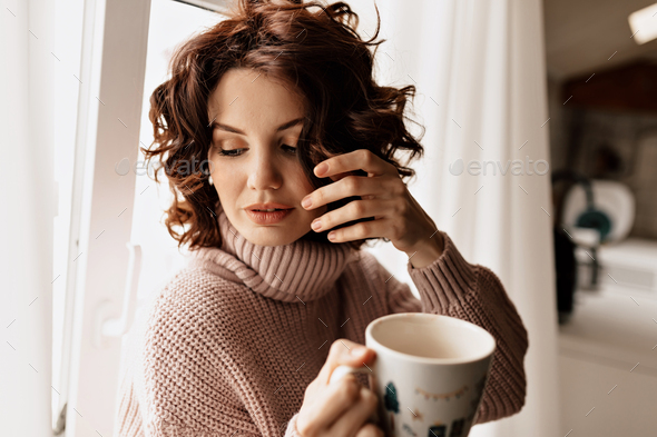 Close up inside portrait of romantic lovely girl with curly hair wearing soft sweater - Stock Photo - Images
