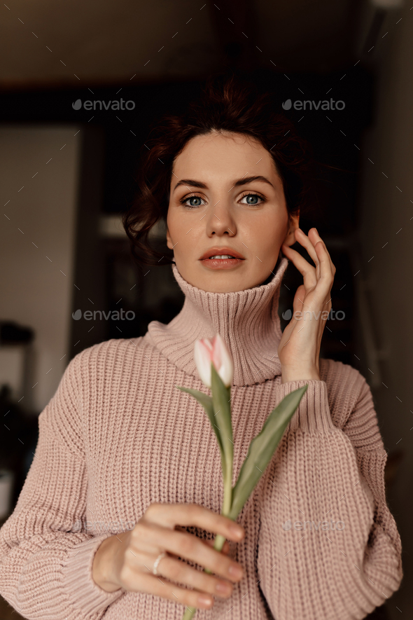 portrait of gorgeous young dark haired woman wearing soft pink sweater holding a tulip - Stock Photo - Images