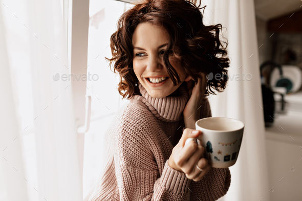 Happy charming girl with short wavy hairstyle drinking tea near the window and enjoying weekend time - Stock Photo - Images