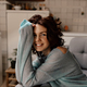 Close up portrait of charming smiling girl with curls resting at home on the coach and having fun - PhotoDune Item for Sale