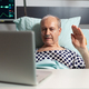 Cheerful sick senior man waving at camera during video conference - PhotoDune Item for Sale