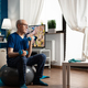 Senior man training body resistance doing arms exercise sitting on swiss ball in living room - PhotoDune Item for Sale
