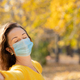 Happy woman wearing protective mask in autumn park - PhotoDune Item for Sale