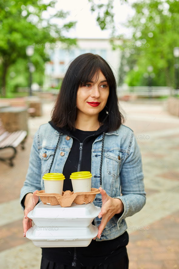 Woman walking in the park, holding a take away food and coffee - Stock Photo - Images