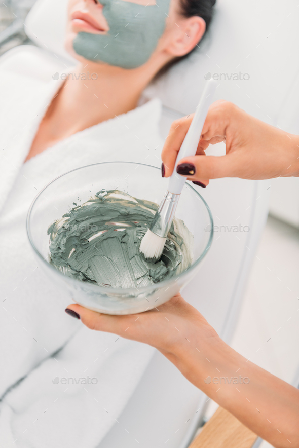selective focus of cosmetologist with clay mask in bowl and brush in spa salon - Stock Photo - Images