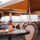 bottle of champagne, two glasses and delicious desserts on table in outdoor cafe - PhotoDune Item for Sale
