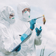 scientists in protective masks and suits examining fish and writing in clipboard against cloudy sky - PhotoDune Item for Sale