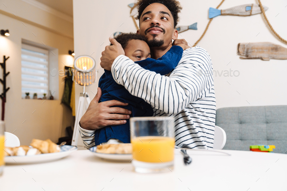 African american father and son hugging while having breakfast - Stock Photo - Images