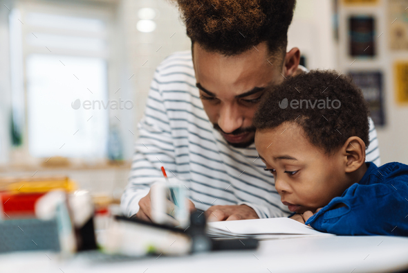 Serious african american father doing homework with his focused son - Stock Photo - Images