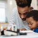 Serious african american father doing homework with his focused son - PhotoDune Item for Sale