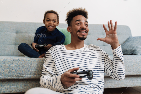 Excited african american father and son gesturing while playing game - Stock Photo - Images