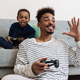 Excited african american father and son gesturing while playing game - PhotoDune Item for Sale