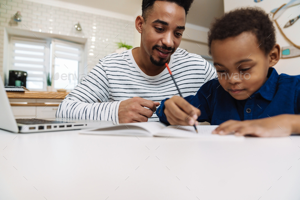Pleased african american father doing homework with his focused son - Stock Photo - Images