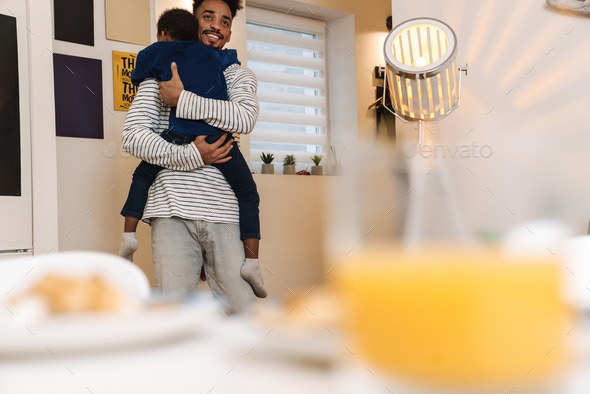 Young african father holding his son while standing - Stock Photo - Images