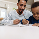 Pleased african american father doing homework with his focused son - PhotoDune Item for Sale