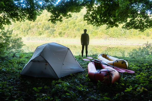 Man near tent and packrafts in forest camp - Stock Photo - Images
