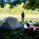 Man near tent and packrafts in forest camp - PhotoDune Item for Sale