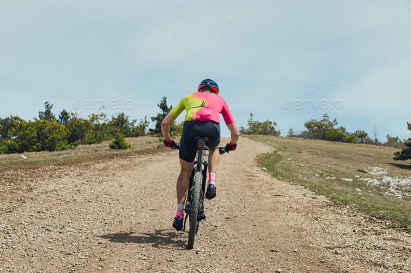 back male athlete on mountain bike - Stock Photo - Images