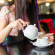 Young woman pouring tea from teapot into cup sitting at table in restaurant, close-up. - PhotoDune Item for Sale
