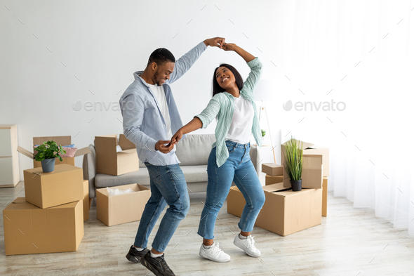 Happy affectionate black spouses dancing in their new apartment among cardboard boxes on moving day - Stock Photo - Images
