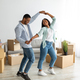 Happy affectionate black spouses dancing in their new apartment among cardboard boxes on moving day - PhotoDune Item for Sale