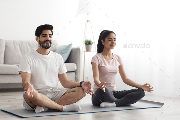 Happy couple doing exercises on quarantine at home, self-isolation together, stretching, exercise - Stock Photo - Images