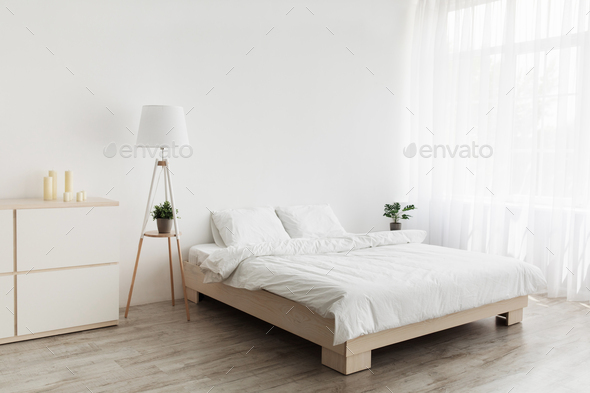 Simple modern design, ad, offer. Double bed with white pillows and soft blanket, lamp, furniture on - Stock Photo - Images
