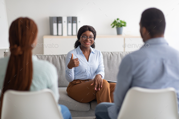 Successful therapy. Professional female psychologist gesturing thumb up while working with young - Stock Photo - Images
