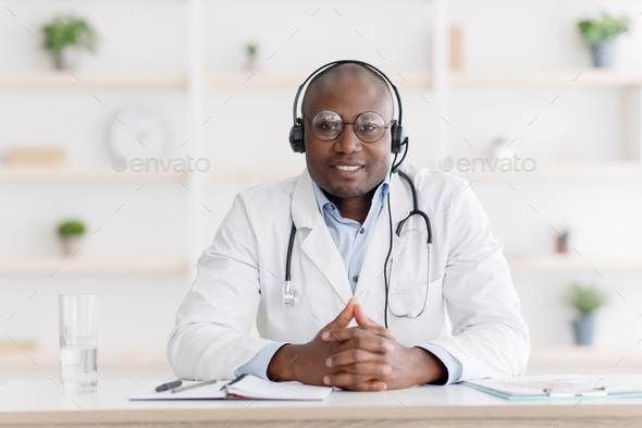 Visit to doctor remotely, online consultation. African american man in white coat with headphones - Stock Photo - Images