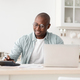 Paying bills, taxes at home online during covid-19 pandemic. Mature african american man with - PhotoDune Item for Sale