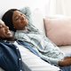 Time To Relax. Happy Black Couple Resting On Comfortable Couch At Home - PhotoDune Item for Sale
