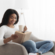 Free time to relax. Calm black woman relaxing on comfortable chair with paper book and holding cup - PhotoDune Item for Sale