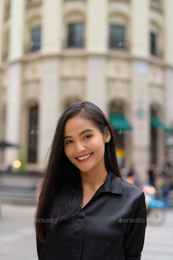 Vertical portrait of beautiful Asian businesswoman smiling outdoors in city street - Stock Photo - Images