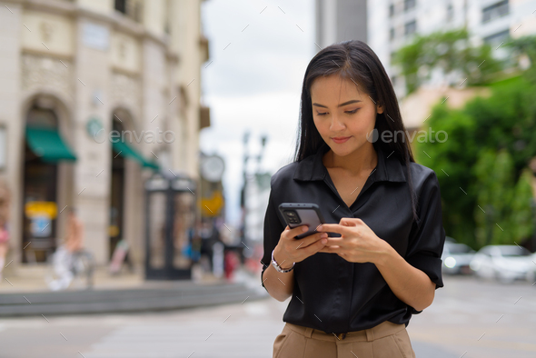 Asian businesswoman outdoors in city street using mobile phone while texting - Stock Photo - Images