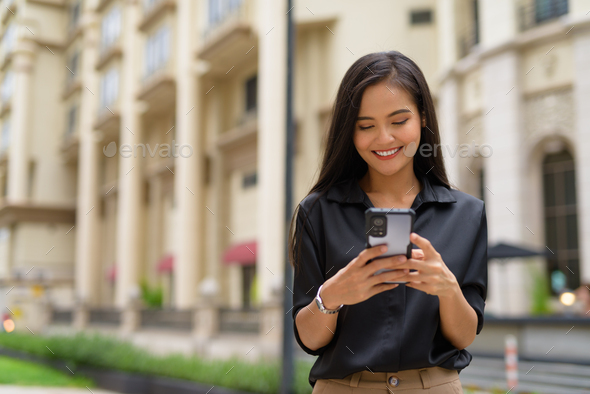 Asian businesswoman outdoors in city street using mobile phone while smiling and texting - Stock Photo - Images