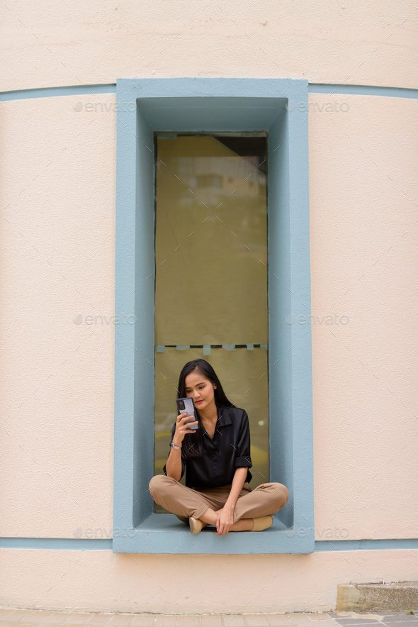 Asian businesswoman sitting and relaxing while using mobile phone in city - Stock Photo - Images