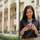 Asian businesswoman outdoors in city street using mobile phone while smiling and texting - PhotoDune Item for Sale