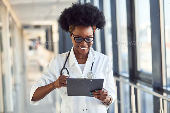 Young african american female doctor in white uniform with stethoscope - Stock Photo - Images