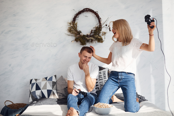 Young lovely couple together at home playing video games on bed with popcorn at weekend time - Stock Photo - Images