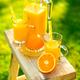 Two glasses of tasty freshly squeezed orange juice on garden stool - PhotoDune Item for Sale