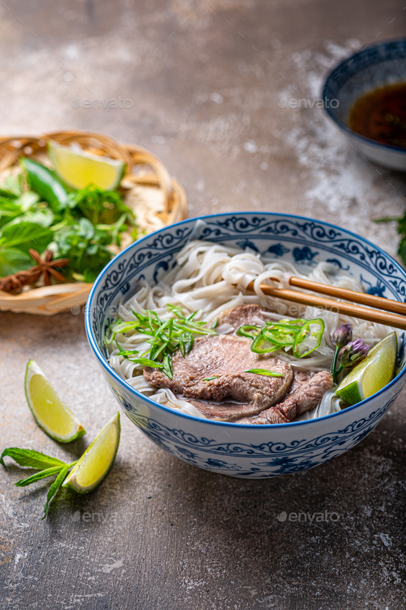 Close view of pho bo in traditional bowl, garnished with basil, mint, lime, on concrete background - Stock Photo - Images