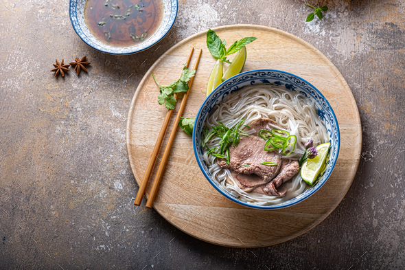 Top view of pho bo vietnamese rice noodle soup with herbs and sauce - Stock Photo - Images