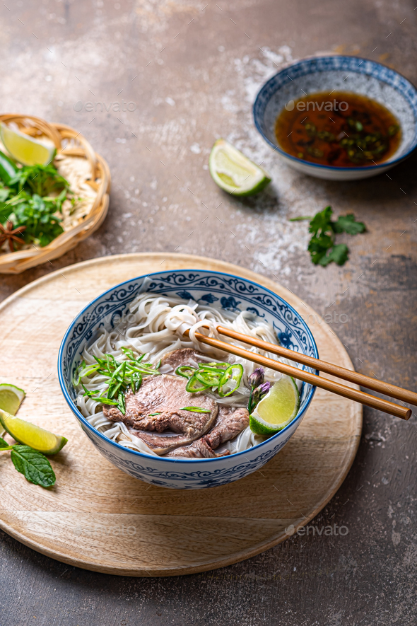 Traditional vietnamese noodle soup pho in bowl, garnished with basil, mint, lime, on concrete - Stock Photo - Images